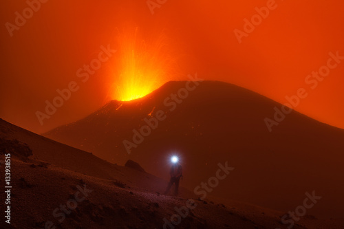 Tuinposter Rood A man wearing a head lamp by an erupting volcano.