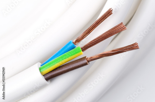 Electrical power cable macro photo. IEC standard color code. Cross-section with cable jacket, wire insulations in brown, blue and yellow-green color with flexible stranded copper wires. Close up.