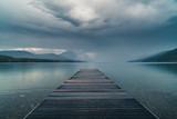 Dock overlooking a calm overcast lake. - 133945719