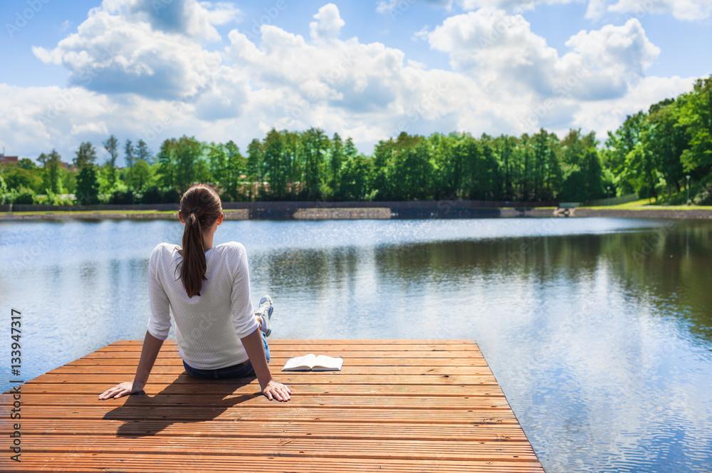 Fototapeta Woman relaxing by a beautiful lake.