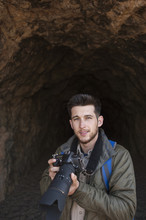 Portrait Of Confident Male Hiker Holding Camera Against Rock