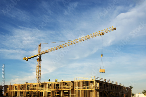 Crane at construction site against cloudy sky
