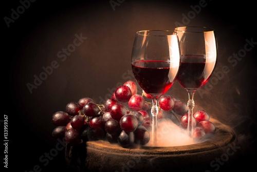 dwa-kieliszki-wina-wsrod-winogron-na-beczce