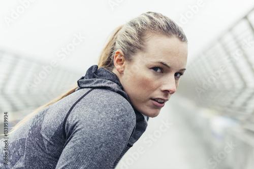 Portrait of tired female athlete on bridge
