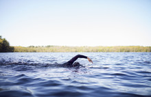 Woman Swimming In Lake Against...