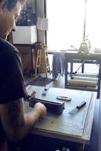 Cropped Image Of Male Lithograph Worker Using Paint Roller At Workshop