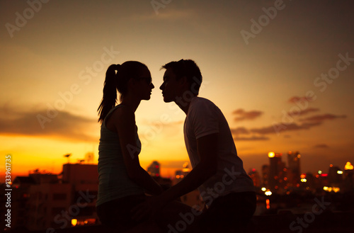 Fotografie, Obraz  Young couple kissing at twilight.