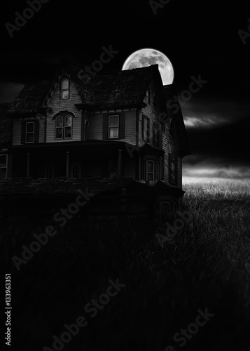 Photo  Back and white haunted house in creepy dark night with moon.