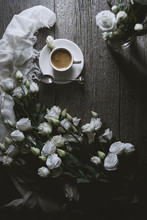 Overhead View Of Coffee With White Roses On Wooden Table