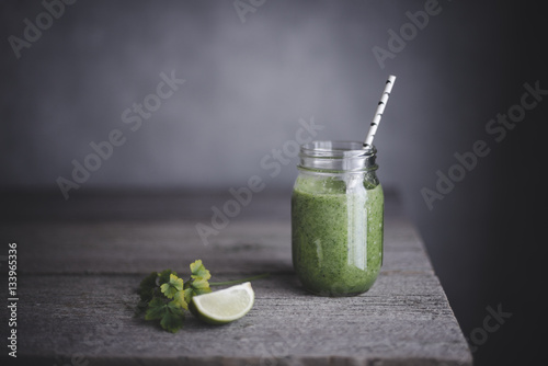 Healthy green smoothie in mason jar with lime on table