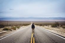 Rear View Of Man Standing On Empty Highway Looking Towards Horizon
