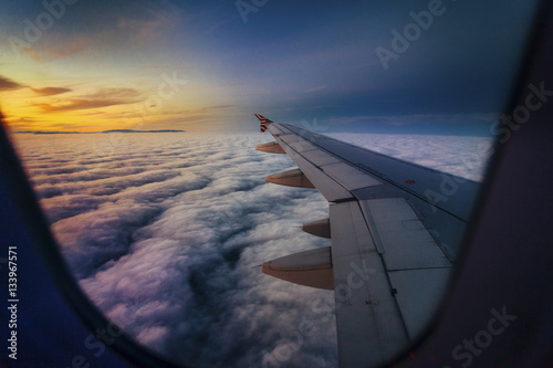 Scenic view of clouds seen through airplane window during sunset