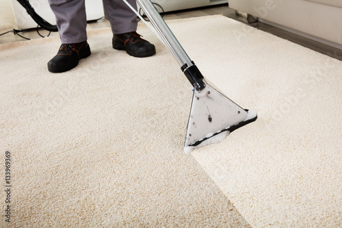 Person Cleaning Carpet With Vacuum Cleaner Wallpaper Mural