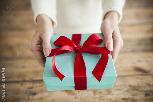 The woman is handing a gift box Fototapeta