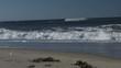 Foamy waves crashing on beach medium shot slow motion