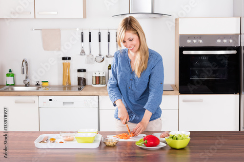 Staande foto Koken Woman Cutting Vegetable On Chopping Board