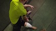 Top view of amputee weightlifter with artificial foot sitting on bench in the gym and doing dumbbell curls