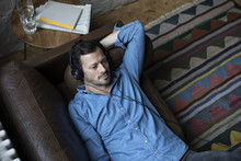 Man Lying On Couch, Wearing Headphones