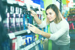 young girl customer looking for effective mouthwash in supermark