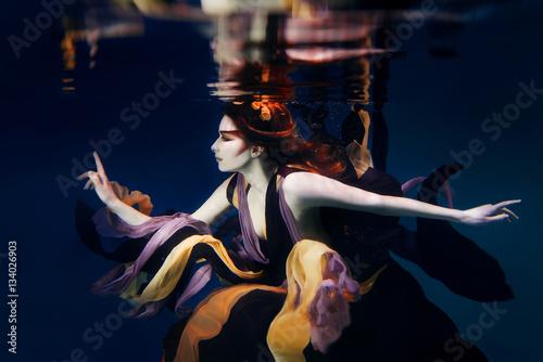 dziewczyna-w-kolorowe-ubrania-na-ciemnym-tle-plywanie-pod-woda