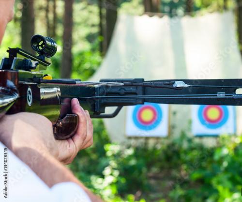Fényképezés Man aiming crossbow at target
