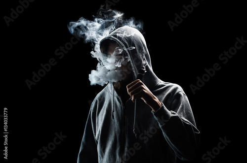 Fotografía One man in the hood vaping e-cigarette and blowing a cloud.