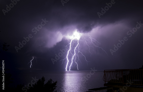 Color thunderbolt from storm clouds above sea with reflection in the water in Croatia Wallpaper Mural