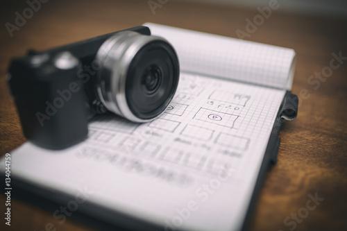 Fototapeta Small digital camera on notepad