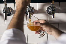 A Bartender Pours A Beer At An...