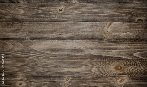 Tuinposter Hout Old weathered wood surface with long boards lined up. Wooden planks on a wall or floor with grain and texture. Dark neutral tones with contrast.