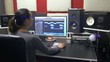 Lady produces electronic music in project in a producing studio.