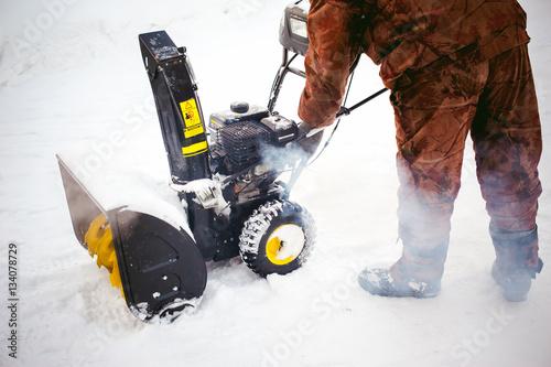 man starts the engine snow blower Wallpaper Mural