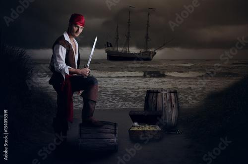 Photo Jeune pirate posant le pied sur un tonneau