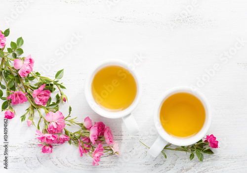Poster Muguet de mai Two cups of tea and branch of small pink roses on rustic table.