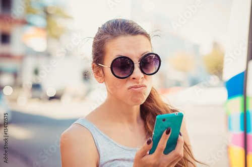 Fotografia, Obraz  Portrait of an annoyed and frustrated young woman on the phone isolated on city scape background
