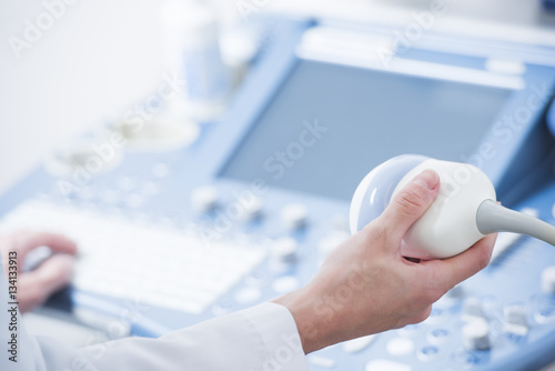 Fototapeta  young woman doctor's hands close up preparing for an ultrasound device scan