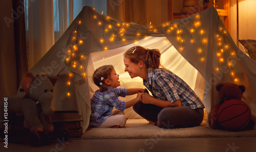 Fototapeta happy mother and daughter playing at home in tent .