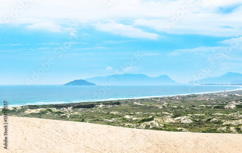 Fotografie, Obraz  Seascape: Beach, sand, green vegetation, blue ocean and some mountains on the background