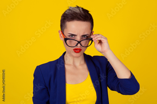 Fotografía  Closeup portrait beautiful young business woman lady looking at you camera over glasses gesture skeptically isolated yellow background