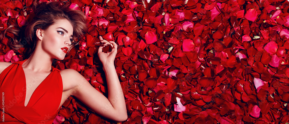 Fototapety, obrazy: Valentine's Day. Loving girl. The girl in a red dress lying on the floor in the petals of red roses. Background of red rose petals. Red lipstick on the lips from the beautiful girl.