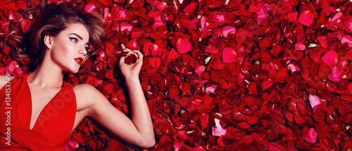 plakat Valentine's Day. Loving girl. The girl in a red dress lying on the floor in the petals of red roses. Background of red rose petals. Red lipstick on the lips from the beautiful girl.