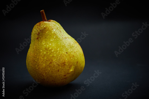 Fresh yellow peer on black background Poster