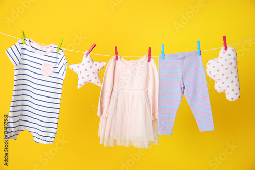 clothesline with hanging baby clothes on yellow background buy