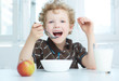 Boy eating cereal while having breakfast in the kitchen.