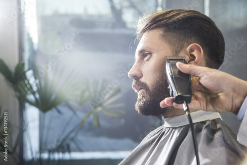Fototapeta man having his beard trimmed