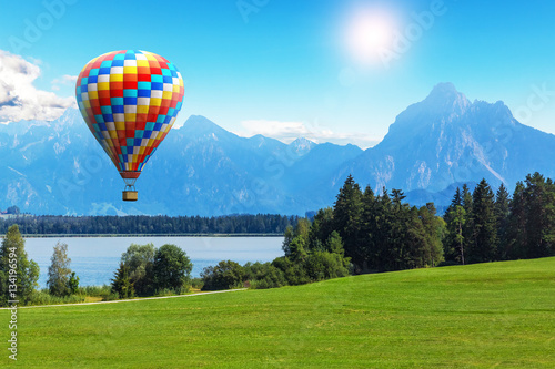 Photo sur Aluminium Montgolfière / Dirigeable Scenic summer landscape with hot air balloon, lake and mountains