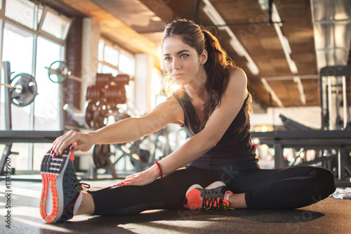 Fotografiet Flexible young woman stretching her right leg in gym.