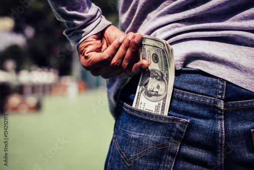 Fotografía  Man hand is putting money in the pocket.