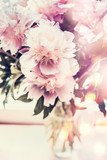 Lovely peonies bunch in glass vase on table with bokeh lighting. Romantic flowers bouquet, front view, pastel color