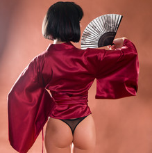 Sexy Geisha In Japanese Red Kimono With A Fan. Back View Female